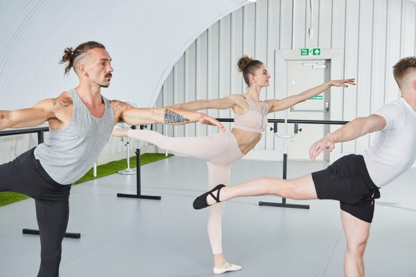 BC ballet based training is a comprehensive online barre workout programme that will develop strength, balance and flexibility while exercising at home. Here both men and women are doing an arabesque used in classical ballet to strengthen the glutes and back while building core strength for balance and stability.